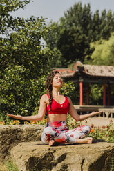 Young woman practicing Pilates in an urban park - NMSF00222