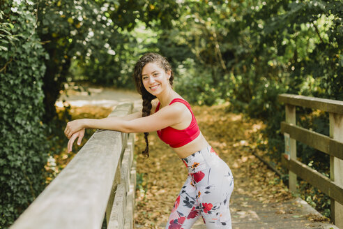 Young woman smiling during break, after practicing Pilates in an urban park - NMSF00243