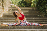Young woman practicing Pilates in an urban park, spagat on steps - NMSF00246