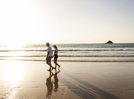 Young couple doing a romantic beach stroll at sunset - UUF15097