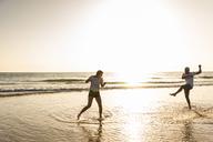 Young couple having fun at the beach, splashing water in the sea - UUF15100
