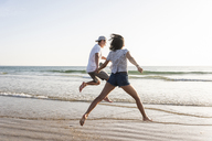 Young couple having fun on the beach, running and jumping at the sea - UUF15106