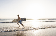 Young man running on beach, carrying surfboard - UUF15115