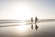 Young couple running on beach, carrying surfboard - UUF15121