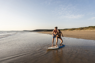 Young man showing young woman how to surf on the beach - UUF15130