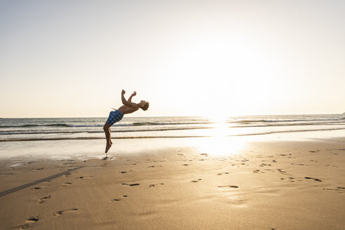 Young man doing somersaults on the beach - UUF15133