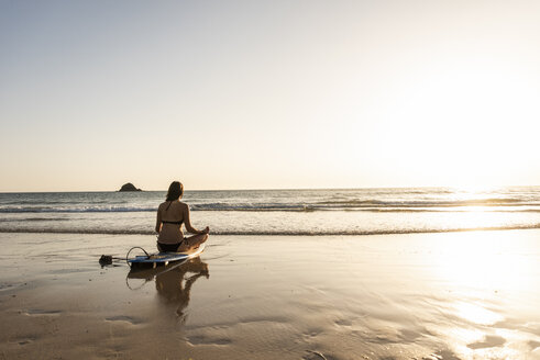 Young woman practicing yoga on the beach, sitting on surfboard, meditating - UUF15136