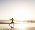 Young woman practicing yoga on the beach, sitting on surfboard, meditating - UUF15142