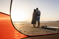 Romantic couple camping on the beach, embracing at sunset - UUF15145