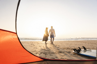 Romantic couple camping on the beach, doing a beach stroll at sunset - UUF15148