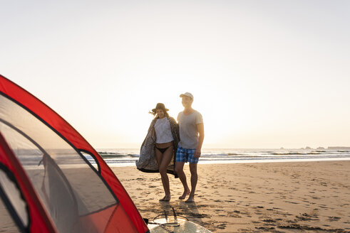 Romantic couple camping on the beach, doing a beach stroll at sunset - UUF15151