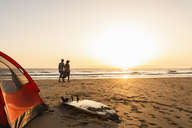 Romantic couple camping on the beach, doing a beach stroll at sunset - UUF15154
