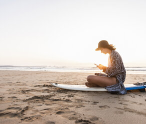 Young woman sitting on surfboard at the beach, using smartphone - UUF15160
