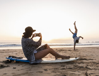Young woman sitting on surfboard, taking pictures of young man, practicing handstands on the beach - UUF15163