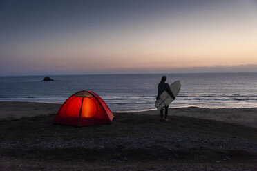 Young woman camping on the beach, carrying surfboard at night - UUF15166