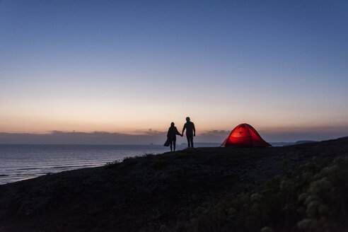 Romantic couple camping on the beach, walking in twilight, holding hands - UUF15169