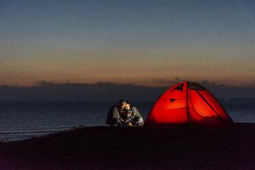 Romantic couple camping on the beach, using smartphone - UUF15172