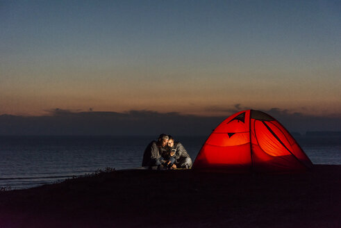 Romantic couple camping on the beach, using smartphone - UUF15172