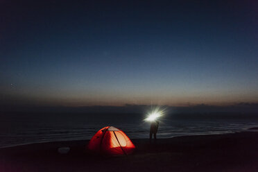 Young man camping on the beach, using flashlight - UUF15175