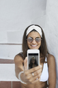 Portrait of smiling young woman wearing white bikini taking selfie with smartphone - IGGF00589