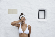 Young woman wearing white bikini top leaning against white wall covering eyes with her hand - IGGF00592