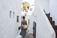 Spain, Menorca, Binibequer, back view of woman walking in an alley - IGGF00598