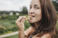 Portrait of woman eating white currants - KMKF00546