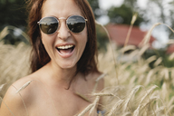 Portrait of happy woman wearing sunglasses in wheat field - KMKF00552