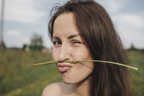 Portrait of woman balancing plant stalk on her mouth twinkling - KMKF00561