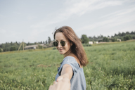 Smiling woman wearing sunglasses holding hand of partner in rural field - KMKF00564
