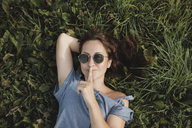 Portrait of smiling woman wearing sunglasses lying in grass - KMKF00570