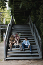 Friends with skateboard relaxing on stairs outdoors - MAUF01683