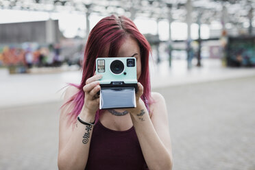Young woman taking photo with instant camera outdoors - MAUF01692