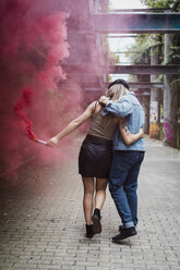 Young couple with smoke torch walking outdoors - MAUF01698