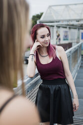 Smiling young woman with dyed hair standing on footbridge - MAUF01713