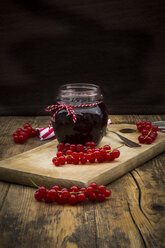 Jam jar of currant jelly and red currants on wooden board - LVF07413