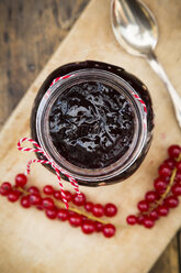 Jam jar of currant jelly and red currants on wooden board - LVF07416