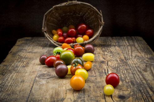 Basket of Heirloom tomatoes on wood - LVF07422