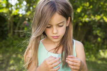 Portrait of serious little girl in the garden - LVF07425
