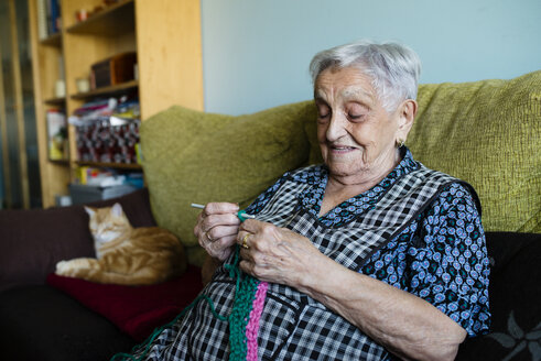 Portrait of crocheting senior woman sitting on couch besides her sleeping cats - RAEF02139