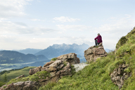Austria, Tyrol, Fieberbrunn, Wildseeloder, woman sitting on stone with view on mountainscape - PSIF00065
