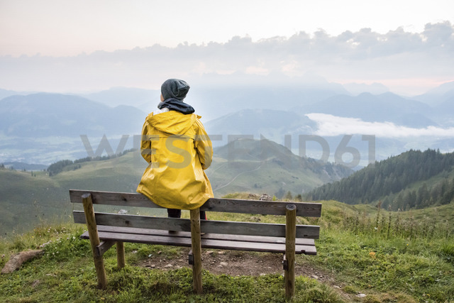 Austria, Tyrol, Fieberbrunn, Wildseeloder, woman sitting on bench with view on mountainscape - PSIF00068 - Petra Silie/Westend61