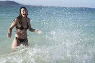 Happy carefree young woman splashing in the sea - PACF00083
