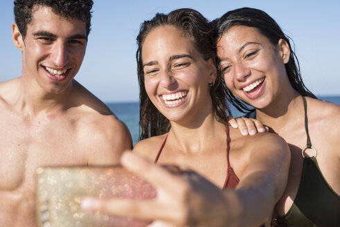 Happy friends taking selfies on the beach - PACF00092