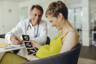 Pregnant woman discussing ultrasonic scans with her doctor - MFF04471