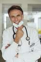 Portrait of a doctor, removing surgical mask, smiling - MFF04474
