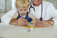 Toddler sitting on doctor's lap, while filling in immunization card - MFF04477