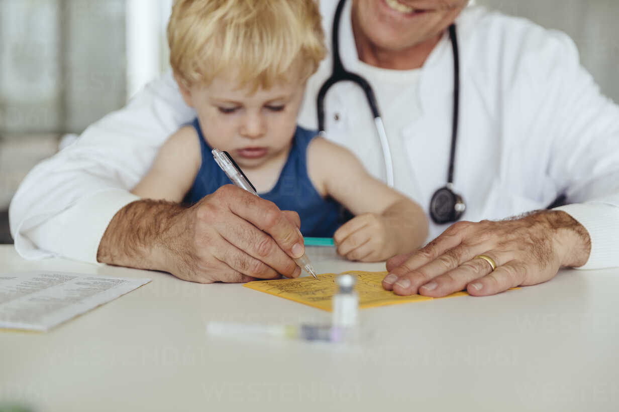 Toddler sitting on doctor's lap, while filling in immunization card - MFF04477 - Mareen Fischinger/Westend61
