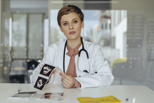 Female doctor sitting at desk, showing ultrasound scan of a fetus - MFF04510