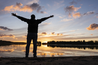 Finland, Kajaani, Man watching sunset at the river with arms outstretched - KKAF01723